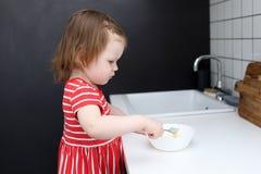 Os 2 anos bonitos da menina ajudam a cozinhar a cozinha da omeleta em casa Imagem de Stock