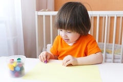 Os 2 anos bonitos das pinturas do menino com cera escrevem Fotografia de Stock