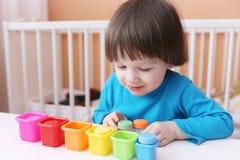 Os 2 anos bonitos do menino classificam brinquedos pela cor Fotos de Stock