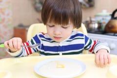 Os 2 anos bonitos do menino comem o papa de aveia da semolina Imagens de Stock Royalty Free