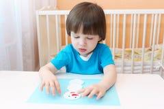 Os 2 anos bonitos do menino fazem o boneco de neve da almofada de algodão Imagem de Stock