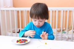 Os 2 anos bonitos do menino fizeram grânulos coloridos em casa Foto de Stock