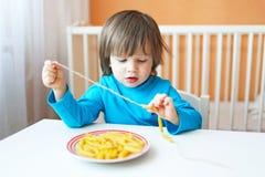Os 2 anos bonitos do menino fizeram grânulos do macarrão em casa Foto de Stock Royalty Free