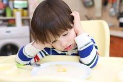 Os 2 anos bonitos do menino não querem comer o papa de aveia da semolina Imagens de Stock Royalty Free