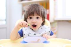 Os 2 anos bonitos do menino têm o jantar Imagens de Stock Royalty Free