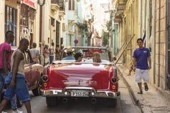 Os anos 50 convertíveis vermelhos Havana do táxi dos povos da cena da rua Imagem de Stock