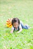 Os anos de idade bonitos da menina 2-3 que jogam a bola no jardim fotos de stock