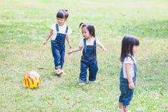 Os anos de idade bonitos das crianças 2-3 que jogam a bola no jardim Fotografia de Stock