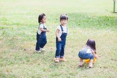 Os anos de idade bonitos das crianças 2-3 que jogam a bola no jardim imagem de stock royalty free
