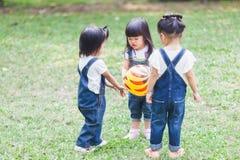 Os anos de idade bonitos das crianças 2-3 que jogam a bola no jardim fotografia de stock royalty free