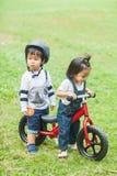 Os anos de idade bonitos das crianças 2-3 que montam o Strider no jardim Fotos de Stock