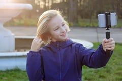 Os anos de idade bonitos de sorriso da menina 9-11 do preteen que tomam um selfie fora Criança que toma um autorretrato com telef Fotos de Stock