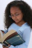 Os anos de idade seis bonitos livro de Readign dos vidros no grande Imagens de Stock
