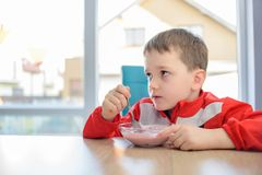 Os 6 anos do menino idoso que come o iogurte de fruto em uma bacia Imagens de Stock Royalty Free