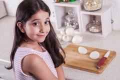 Os 7 anos do Oriente Médio pequenos bonitos da menina idosa estão trabalhando com faca e cebola na cozinha branca Tiro do estúdio Foto de Stock
