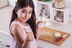 Os 7 anos do Oriente Médio pequenos bonitos da menina idosa estão trabalhando com faca e cebola na cozinha branca Tiro do estúdio Imagens de Stock Royalty Free