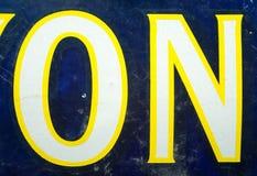 Os anos 30 do vintage resistiram ao esmalte no texto no esmaltado assinam dentro o azul, o amarelo e o branco Fotos de Stock