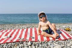 Os 2 anos felizes do menino nos óculos de sol sentam-se na praia de pedra Imagem de Stock