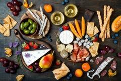Os aperitivos apresentam com os petiscos e vinho italianos dos antipasti nos vidros A variedade do queijo e do charcuterie embarc imagem de stock