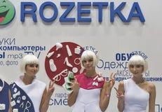 Os apresentadores trabalham na cabine da empresa de Rozetka na ECO 2015, feira profissional a maior da eletrônica em Ucrânia foto de stock royalty free