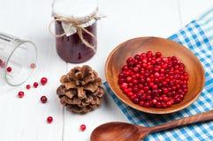 Os arandos na bacia de madeira com colher e doce no frasco no branco surgem Fotos de Stock Royalty Free