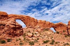 Os arcos gêmeos enormes da rocha aumentam acima do assoalho arenoso do deserto em Utá, EUA foto de stock