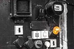 Os armários velhos com fiação e condução por meio de canos do controle de sistema elétrico na fábrica pequena para trabalhos da a imagens de stock