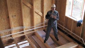 Os arquitetos ou a verificação do construtor planeiam em uma meia casa de quadro construída da madeira Construtor em um canteiro  video estoque