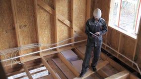 Os arquitetos ou a verificação do construtor planeiam em uma meia casa de quadro construída da madeira Construtor em um canteiro  filme