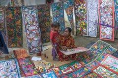 Os artesanatos coloridos estão sendo preparados para a venda na vila de Pingla pelo trabalhador rural indiano da mãe da mulher Imagem de Stock