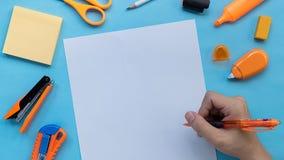 Os artigos de papelaria e destro com o perpare da pena a escrever acima no papel no fundo azul da cor, fim, plano colocam a image foto de stock