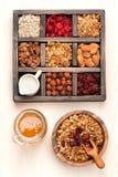 Os artigos do café da manhã - aveia, muesli do granola, porcas, mel, secaram bagas e leite Vista superior Fotografia de Stock Royalty Free