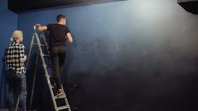Os artistas de um grafitti tiram um contorno em uma parede azul Um homem em escadas prepara uma parede tirando filme