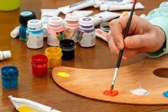 Os artistas entregam pinturas de mistura na paleta Imagem de Stock