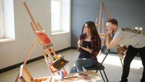 Os artistas pintam imagens no estúdio Os artistas criativos projetaram uma imagem colorida pintada na lona com óleo filme