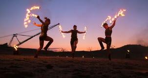 Os artistas profissionais mostram uma mostra do fogo em um festival do verão na areia no movimento lento Quartas acrobatas da pes video estoque