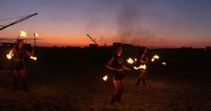 Os artistas profissionais mostram uma mostra do fogo em um festival do verão na areia no movimento lento Quartas acrobatas da pes filme