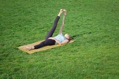 Os asans praticando da ioga da senhora apta na esteira da ioga que coloca dentro gren a grama Imagem de Stock
