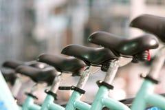Os assentos de bicicleta são alinhados uniformemente em seguido Fotografia de Stock Royalty Free