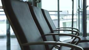 Os assentos na sala de espera no aeroporto, povos vêm ao aeroporto vídeos de arquivo