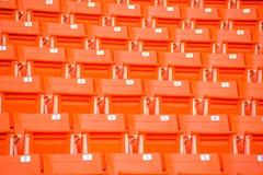 Os assentos vermelhos no estádio pisam bleacher imagem de stock