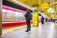 Os assinantes esperam o trem para parar para obter sobre em uma das estações de metro no Tóquio, Japão imagem de stock