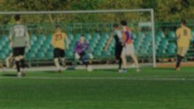 Os ataques e o goleiros do jogador de futebol travam uma bola, jogo de futebol, borrado para o fundo filme