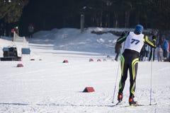 os Atleta-esquiadores correm uma maratona do esqui na floresta do inverno imagens de stock