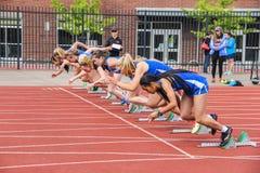 Os atletas da menina começam a raça de 100 medidores Fotografia de Stock