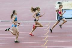 Os atletas da menina correm 400 medidores Fotografia de Stock Royalty Free
