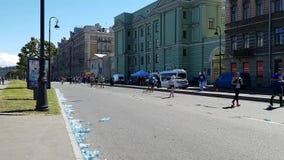 Os atletas dos corredores correm uma maratona através das ruas da metrópole Na borda da estrada rejeitou garrafas de água vídeos de arquivo