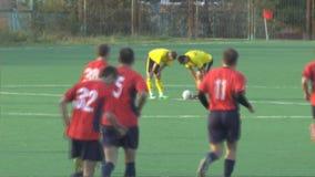 Os atletas dos desconhecidos estão jogando o futebol video estoque