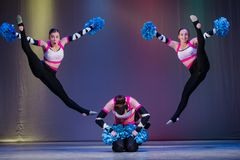 Os atletas executam na fase, líder da claque novos executam no campeonato cheerleading, meninas em um salto, fazer da menina acro foto de stock royalty free