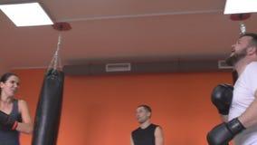 Os atletas menina e homens lutam nas artes marciais do boxe de treino que encaixotam no gym sob a supervisão de um treinador, eng filme
